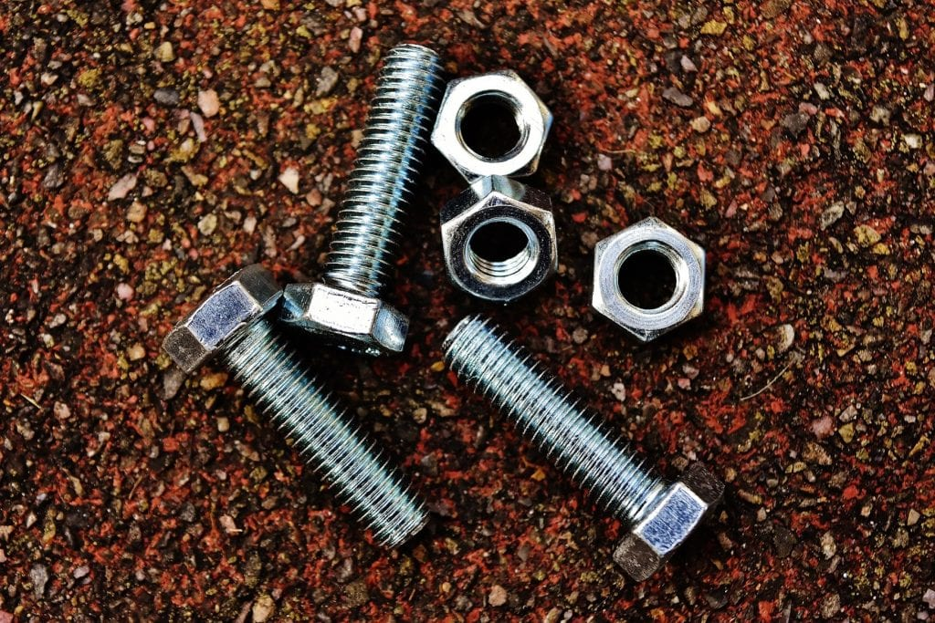 3 nuts and 3 bolts lie on an uneven surface