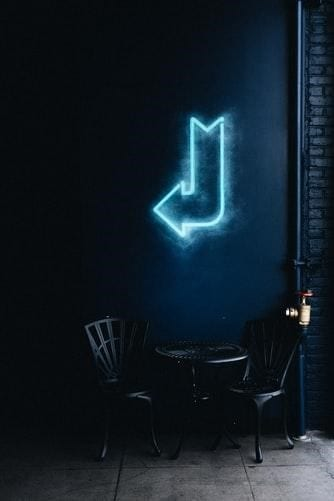 A blue neon arrow sign hanged on a wall to show a specific direction