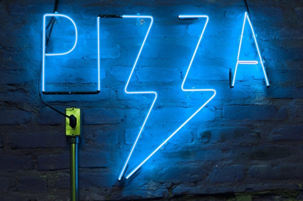 A blue neon sign in the shape of a pizza handing on a wall
