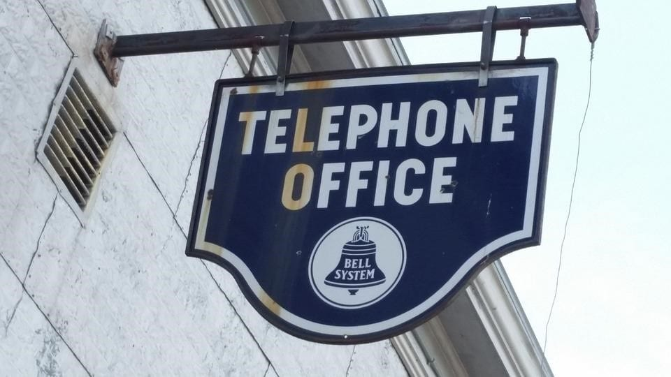 A vintage blue sign of the telephone office of Bell System