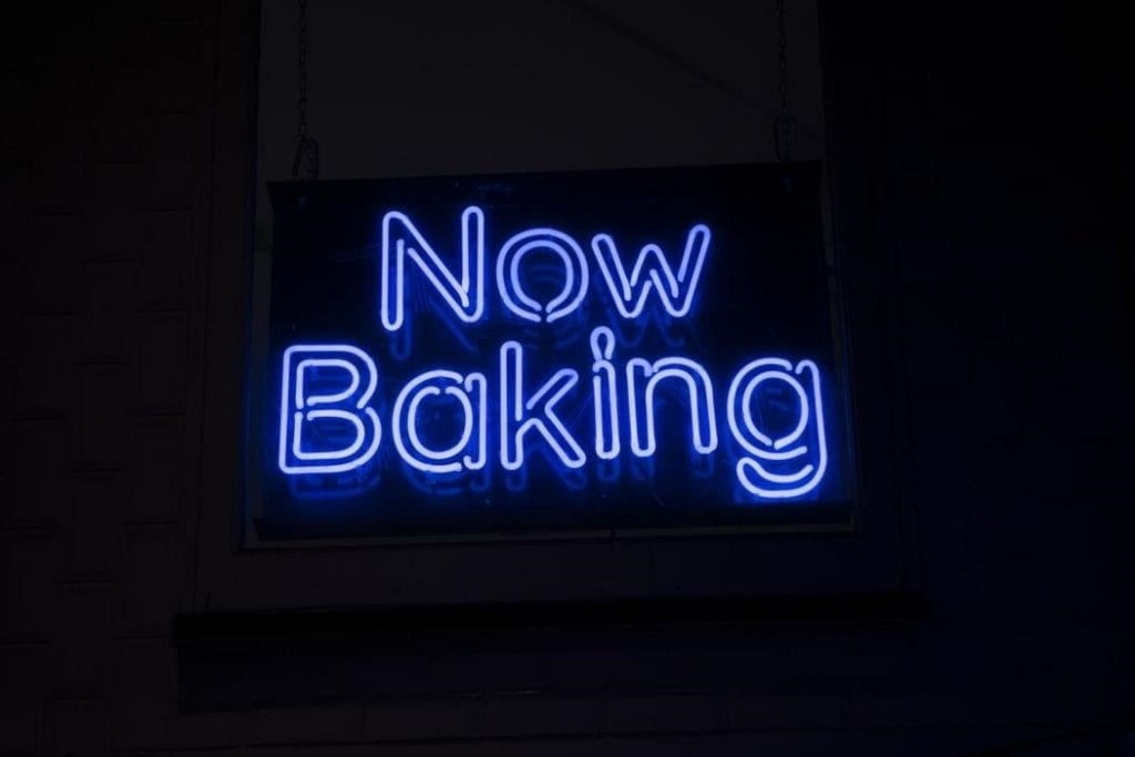 A blue neon sign hanging on a wall that reads 'Now Baking'.