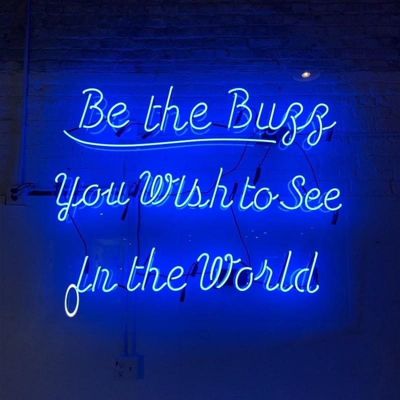 A blue neon sign with an inspirational quote.