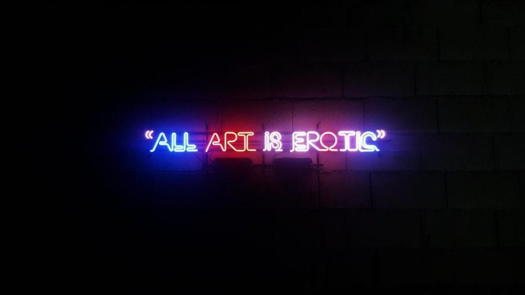 A blue neon sign with a quote about art being erotic.