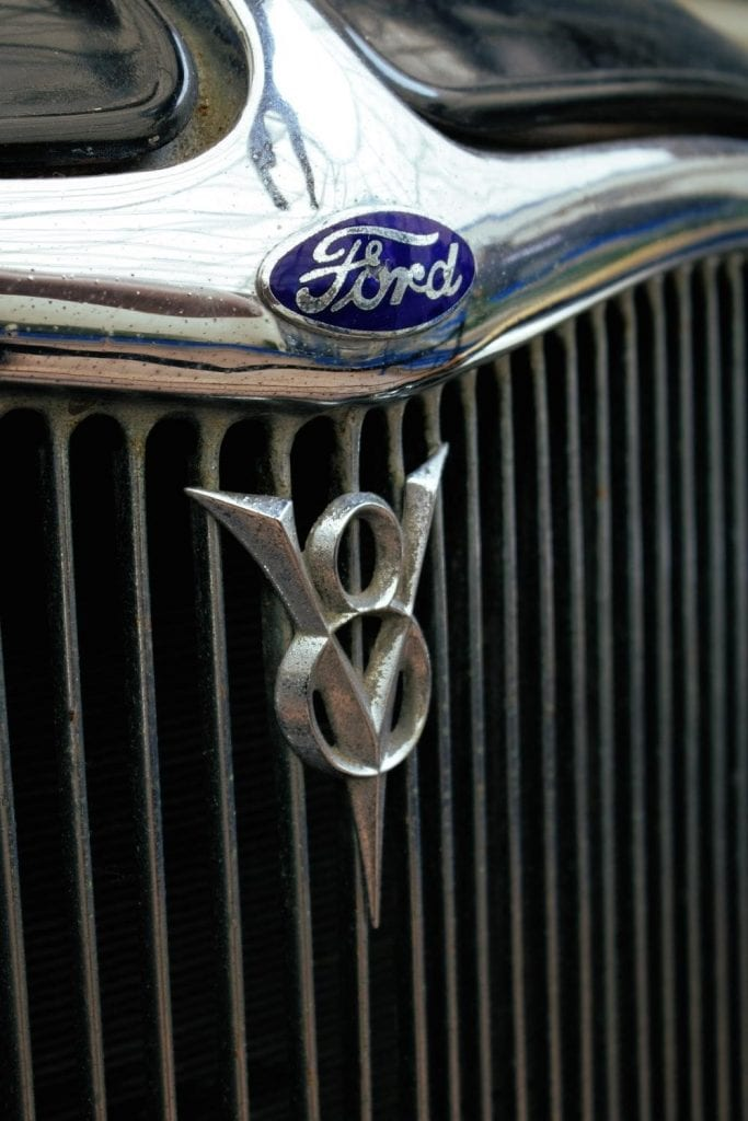 The famous blue Ford logo at the bonnet of a car.